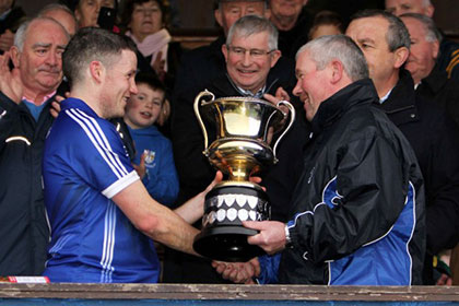 Cratloe chairman Jack Chaplin hands over the Jack Daly cup to captain Martin Martin Murphy.