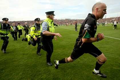 Referee Cormac Reilly gets a Garda escort off the pitch after the game.<br />&#169;INPHO
