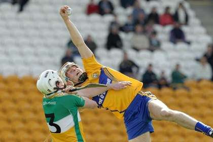 Clare's Aaron Cunningham makes a spectacular catch over the head of Offaly's David Kenny ©INPHO/Morgan Treacy