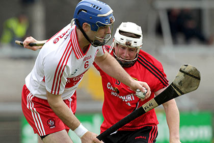 Derry's Liam Hinphey in action with Down's James Coyle. INPHO