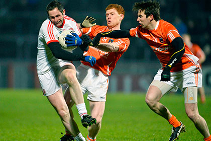 Tyrone's Ronan McNabb is tackled by Tony Kernan with Kyle Carragher of Armagh during the McKenna Cup game at Healy Park. INPHO