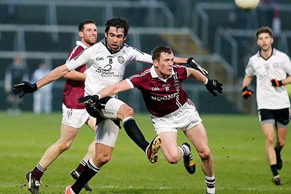 Omagh's Joseph McMahon with Slaughtneil's Patsy Bradley. INPHO