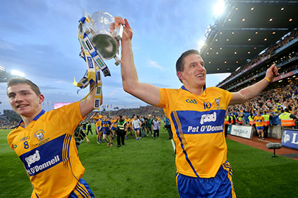 Clare's Colm Galvin and John Conlon celebrate with the Liam McCarthy. INPHO