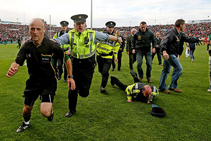 Referee Cormac Reilly leaves the field with a garda escort after the Kerry v Mayo All Ireland semi final replay at Limerick. INPHO