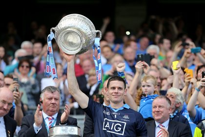 Stephen Cluxton lifts the provincial trophy after being presented with it by Leinster Council chairman John Horan (far left) ©INPHO/Cathal Noonan