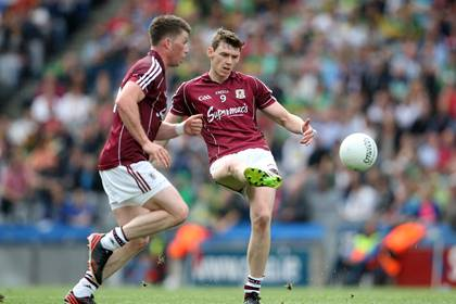 Galway&#39;s Tom Flynn delivers a kick pass alongside team mate Gareth Bradshaw during the 2014 All-Ireland SFC quarter-final.<br />&#169;INPHO/Cathal Noonan.