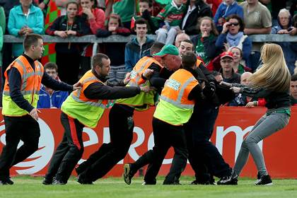Mayo supporter Mick Barrett is led from the pitch during the 2014 All-Ireland SFC semi-final replay against Kerry at the Gaelic Grounds, Limerick.<br />&#169;INPHO/Donall Farmer.