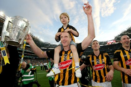 Kilkenny's Henry Shefflin celebrates with his son Henry and The Liam McCarthy Cup ©INPHO/Ryan Byrne