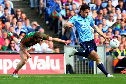 Bernard Brogan of Dublin scores a point despite the efforts of Colm Boyle of Mayo.<br />&#169;INPHO/Donall Farmer.
