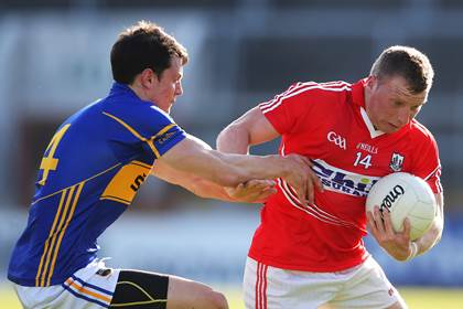 Cork&#39;s Brian Hurley is tackled by Ciaran McDonald of Tipperary.<br />&#169;INPHO/Cathal Noonan.